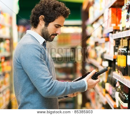 Man in a supermarket choosing a wine