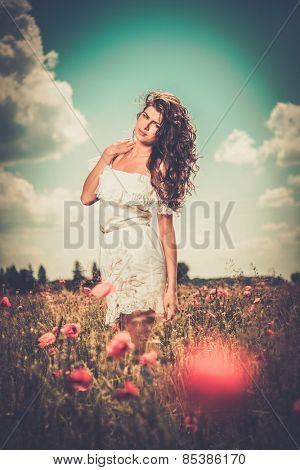 Beautiful young brunette girl wearing white summer dress in poppy filed