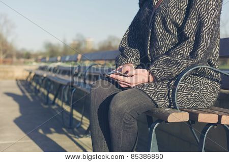 Woman Using Her Phone By Water In Park