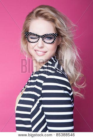 Successful young attractive blonde winking woman wearing glasses