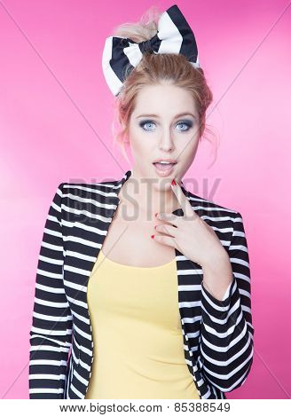 Attractive young surprised woman  on pink background, beauty and fashion concept
