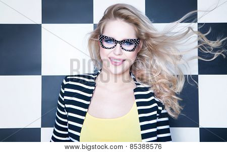 Attractive young woman wearing glasses on checkered background, beauty and fashion concept