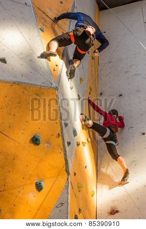 two young people climbing on wall