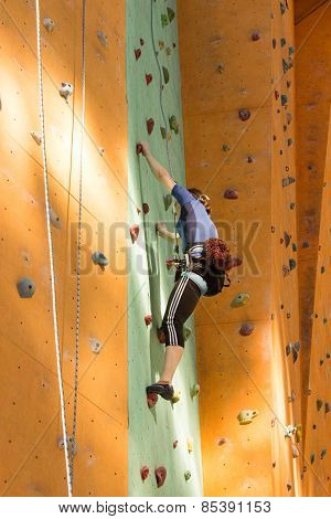 active young woman on rock wall in sport center.
