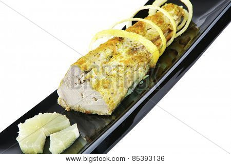 roast tuna chunk with lemon on black porcelain plate