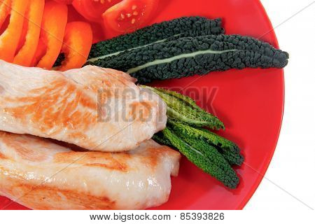 fresh grilled turkey meat fillet steak on red plate with tomatoes pepper green kale and lettuce salad isolated over white background