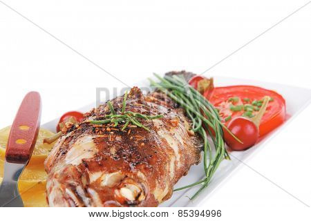 served main course isolated on white: whole fried seabass on plate with lemons,tomatoes and peppers . shallow dof