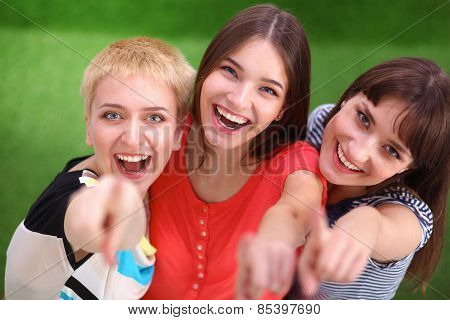 Three happy girls pointing fingers at you choosing