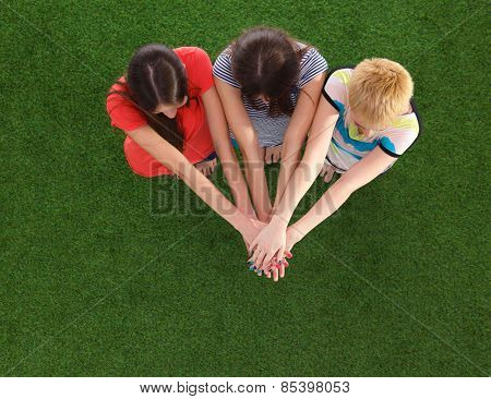 People joining their hands  standing on green grass