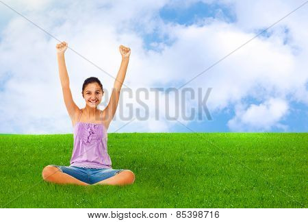 Sitting Teenage Girl On Grass While Rejoices With Arms Up.