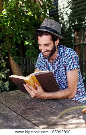 young man relaxing outdoors reading literature novel story book at home