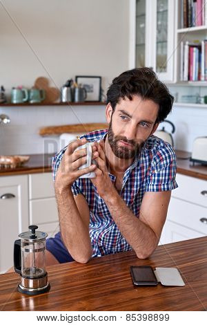 man enjoying french press filter coffee at home kitchen