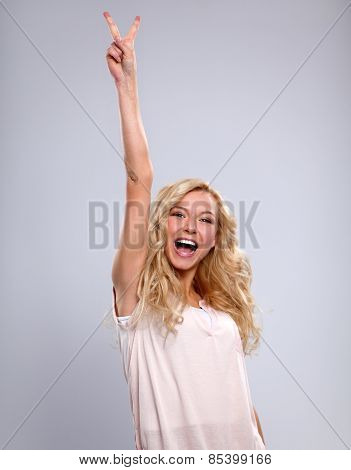 Young emotional woman, standing on gary background