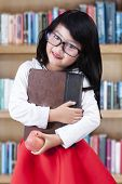 foto of indian apple  - Portrait of lovely little girl standing in the library while holding a book and apple - JPG