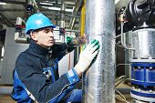stock photo of boiler  - industrial construction worker at boiler room pipe heat insulation work - JPG