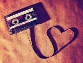 stock photo of heart sounds  - an old dirty grungy scratched up audio cassette tape in the shape of heart  - JPG