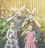 image of bunny ears  - A funny family portrait on Easter of a mother and father wearing bunny ears and holding up silly eyes made from eggs as their children pose eating carrots outside in a garden during the spring season - JPG