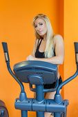 picture of elliptical  - Young sports woman doing exercises on an elliptical trainer in the gym - JPG