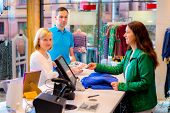 foto of over counter  - young woman and man in the clothes shop over the counter - JPG