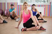 stock photo of stretch  - Photo of fit people stretching legs during fitness classes - JPG