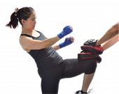 stock photo of boxing  - Woman hitting boxing pads with a knee - JPG