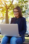 picture of work bench  - Portrait of young student girl in glasses sitting on the campus bench while use laptop gadget during her class break - JPG
