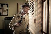 foto of peek  - Attractive spy agent peeking from an office window film noir. ** Note: Shallow depth of field - JPG