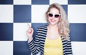 image of casual wear  - Attractive young woman wearing sunglasses on checkered background - JPG