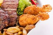 image of leafy  - Wholesome platter of mixed meats including grilled steak crispy crumbed chicken and beef on a bed of fresh leafy green mixed salad served with French fries and chutney or BBQ sauce in a dish - JPG