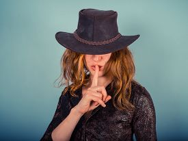 image of hush  - A young woman wearing a cowboy hat is gesturing hush by putting her finger on her lips - JPG
