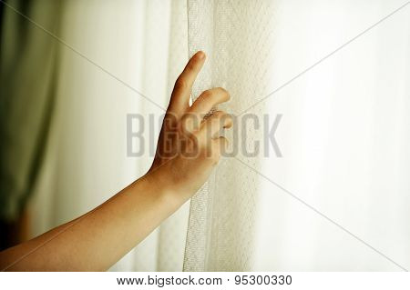 Hand Pulling A Window Curtain