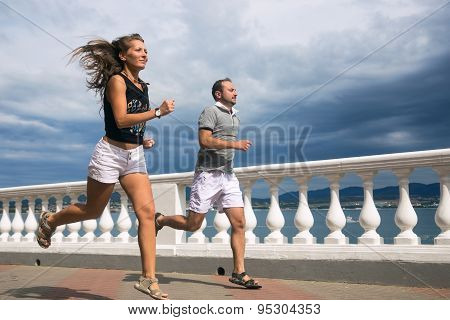 Young sports couple runs along the promenade by the sea