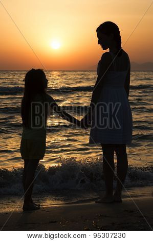 Mother And Daughter Standing At Sunset And Looking At Each Other On Seashore