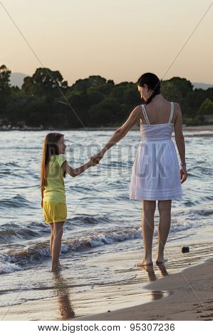Mother And Daughter Walking Along Sea Shore At Sunset And Looking At Each Other