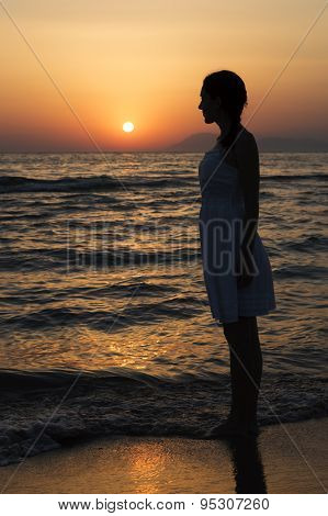 Woman Standing On Seashore And Looking At Sunset