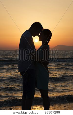 Man And Woman Standing At Sunset And Looking At Each Other On Seashore