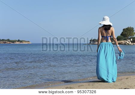 Woman Standing On A Beach And Holding Pair Of Slippers