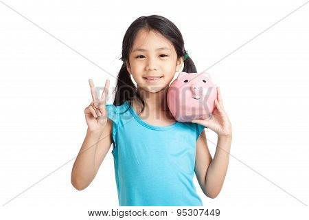 Little Asian Girl Show Victory Sign With Piggy Bank