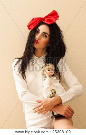 beautiful woman with bright makeup with doll in hands