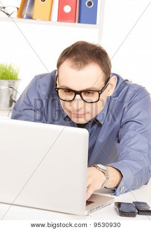 Businessman With Laptop Computer In Office