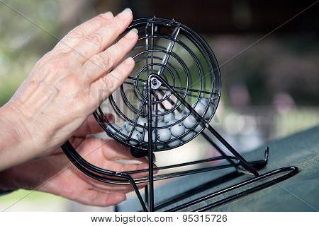 Bingo! A Close-Up of Hands with Bingo Wheel and Balls