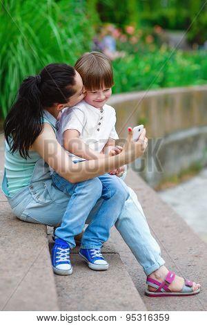 Loving mother kiss son taking self portrait