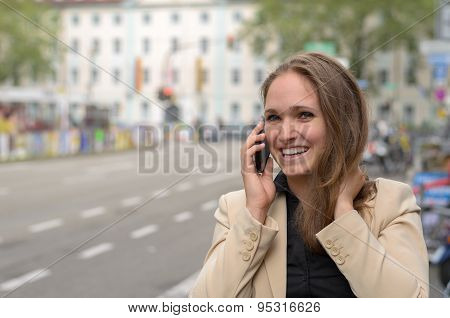 Young Woman Laughing As She Chats On Her Mobile
