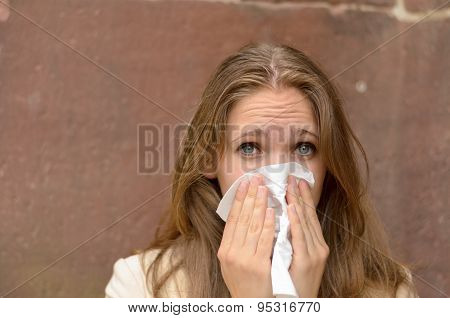 Young Woman Blowing Her Nose On A Handkerchief