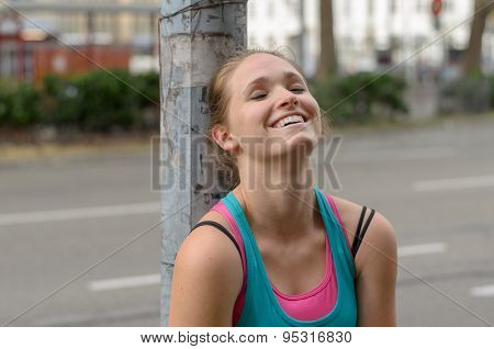 Happy Thoughtful Sporty Woman Leaning Against Post
