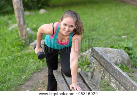 Sporty Young Woman Lifting Dumbbells At The Bench