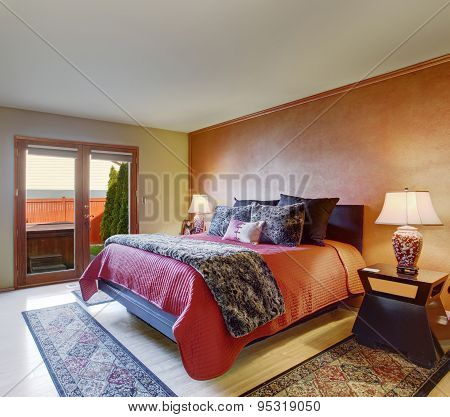 Beautiful Master Bedroom With Red Bedding And Beige Walls.