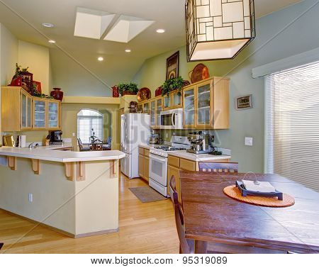 Modernized Kitchen With Light Green Walls And Hardwood Floor.