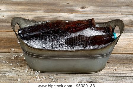 Old Metal Bucket Filled With Beer And Crushed Ice On Rustic Wooden Boards
