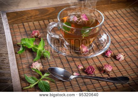 Cup of green tea with mint and roses